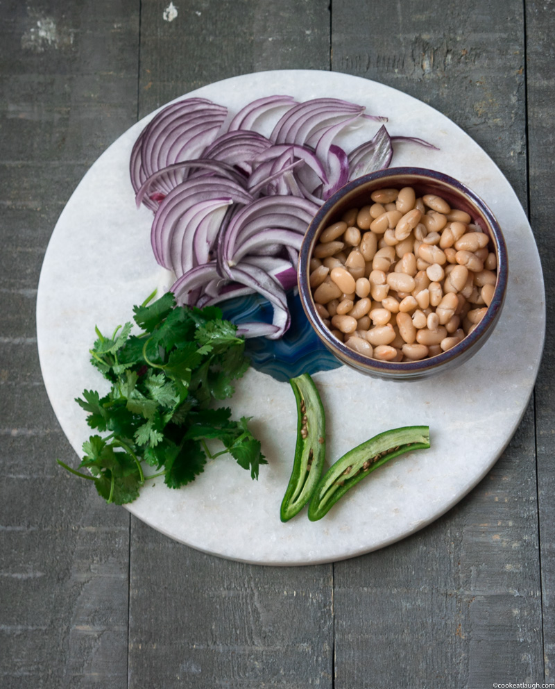 Healthy white bean tostadas! are crunchy, light, and quick to make. The tortillas are baked in the oven and topped with a simple white bean salad. www.cookeatlaugh.com-11
