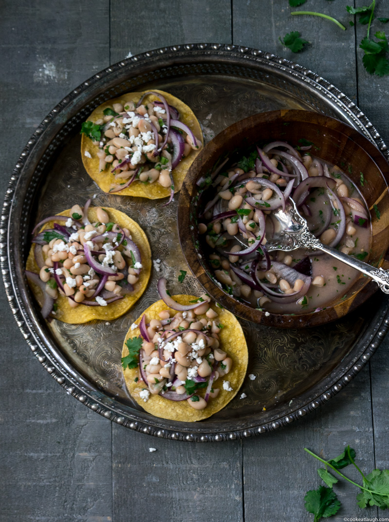Healthy white bean tostadas! are crunchy, light, and quick to make. The tortillas are baked in the oven and topped with a simple white bean salad. www.cookeatlaugh.com-14