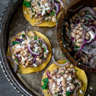 Healthy white bean tostadas! are crunchy, light, and quick to make. The tortillas are baked in the oven and topped with a simple white bean salad. www.cookeatlaugh.com-15